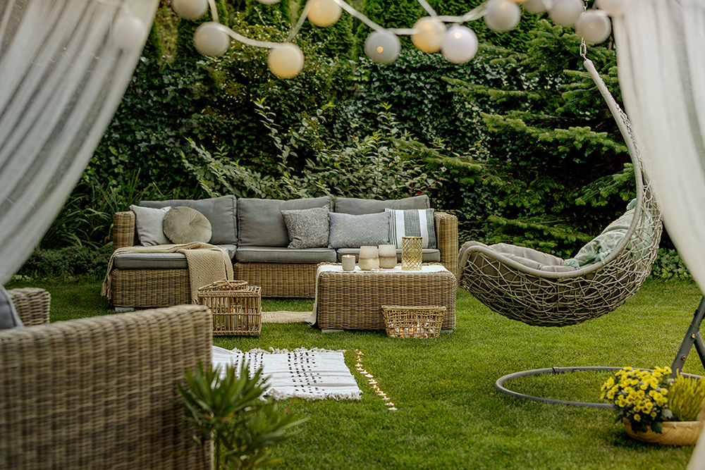 Cozy wicker sofa set and hanging chair in the garden